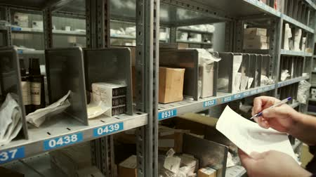 отправка : Warehouse worker makes a note in the documents and takes out a box. Inside are metal racks with numbered cells on shelves.