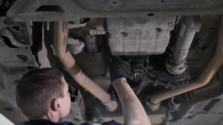 затянуть : Technician carries out diagnostics and repair under body car. Master mechanic of service station is clothes in blue suit and black working gloves. Стоковые видеозаписи