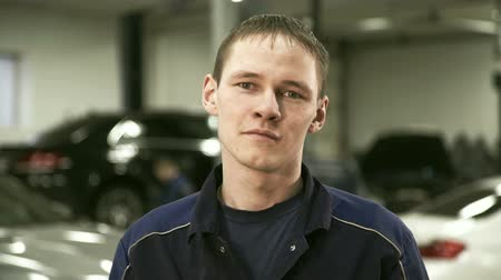честный : Portrait of repairman on a background of car service center. Master looks directly into the camera. He is dressed in a special dark blue uniforms, which is visible under the silver chain around his neck.