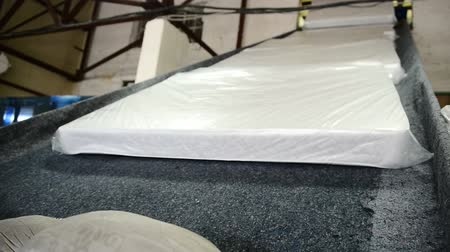 işlenmiş : Orthopedic mattresses move along conveyor belt at factory indoors. Finished production in plastic packaging automatic tape in workshop of modern plant.