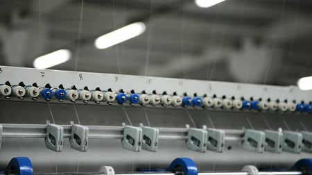 centímetro : plant for making mattresses At sewing factory machine quickly moves threads through rollers. In shop there is a machine in which textiles are intertwined in a certain sequence.