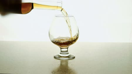 golden color : In glass human pours alcohol from bottle on white background. For tasting sommelier fills container with dark drink.