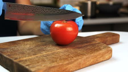 akut : Woman cuts tomato in half with knife in kitchen of house. She puts red ripe fruit on wooden board and cuts it into two pieces slowly using acute steel chopper. Stok Video