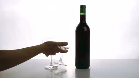estilização : Man and woman put on desk bottle of red wine and glasses indoor. People place on white table bottle filled with elite alcoholic beverage, two elegant glasses and opener.