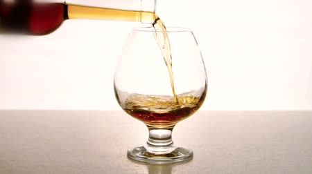 coisas : In an empty glass from bottle alcohol is poured on white background. In wine glass sommelier close-up pours drink for tasting.