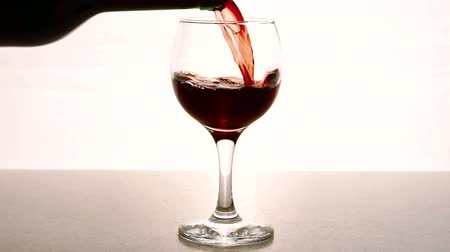 каберне : Man fills transparent glass with red wine in restaurant indoor. Person pours slowly purple alcoholic drink into elegant glass, filling it halfway, since true taste of wine can be felt only if there is enough air in wineglass.