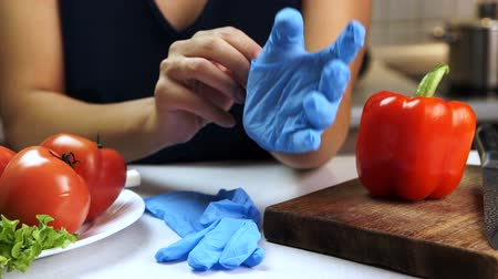 white cloths : Woman at kitchen table puts on sterile gloves for cutting vegetables. Female chef begins cooking food, next there are tomatoes and peppers on wooden board.