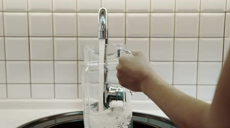 enchimento : Woman fills pitcher with drinking water from metal tap in kitchen of house. She takes transparent glass container, opens silver faucet and clean aqua pours in, quickly.