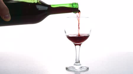 цвет бордо : Person pours red wine into glass in room of appartment. Man fills slowly glasses transparent glass with alcoholic drink, holding bottle by base and tilting it gently. Стоковые видеозаписи