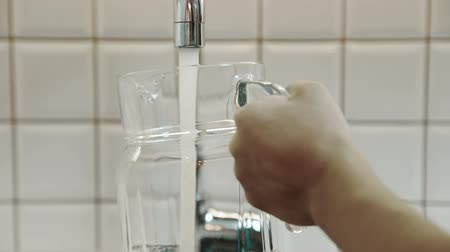 кувшин : Homeowner fills glass jug with tap water indoor. Стоковые видеозаписи