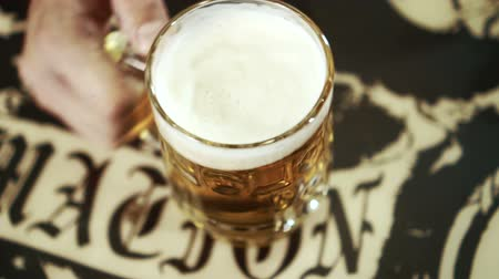 karczma : Male hand puts a mug of beer on the table. Close-up on a wooden painted surface a man puts a beer glass.