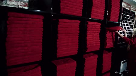 towel folded : Young lady is taking red towel from stock in black shelves in luxury sport center, slow motion. Woman in uniform, with long dark hair is serving the client, who want to have a training and giving him clean cloth to use in bathroom. Stock Footage