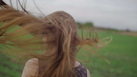 tmavé vlasy : Beautiful healthy woman in dark dress with floral print stands in and then running across green field look back and wind blowing her hair