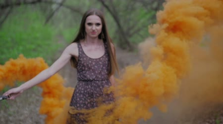 dym : Happy young woman in dark dress with floral print having fun outdoor in summer forest. Beauty girl holding a colorful orange smoke bomb and goes to the camera.wonderful smile.