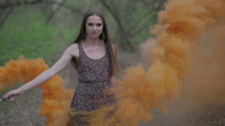 bomba : Happy young woman in dark dress with floral print having fun outdoor in summer forest. Beauty girl holding a colorful orange smoke bomb and goes to the camera.wonderful smile. middle shot slow motion ungraded flat color