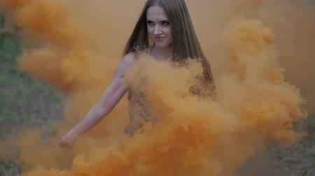 bomba : Happy young woman in dark dress with floral print having fun outdoor in summer forest. Beauty girl holding a colorful orange smoke bomb and goes to the camera.wonderful smile. medium close up slow motion ungraded flat color