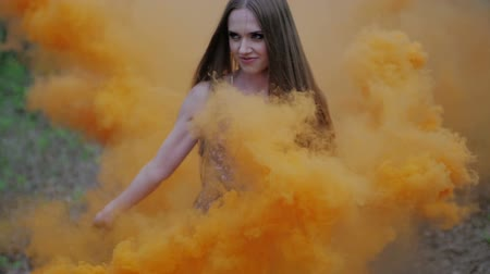 bomba : Happy young woman in dark dress with floral print having fun outdoor in summer forest. Beauty girl holding a colorful orange smoke bomb and goes to the camera.wonderful smile. medium close up slow motion Stock Footage