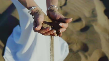 horizonte sobre a água : Woman with sand falling through her hands on beach