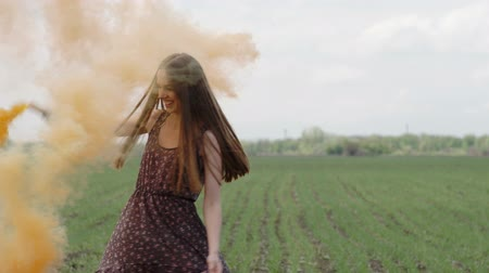 bomba : Happy young woman in dark dress with floral print having fun outdoor in geen field. Beauty girl with orange smoke bomb spinning and laughing. middle shot Stock Footage