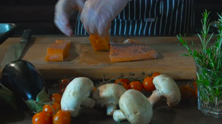 origens : Chef Hand Cuts Salmon Fish Fillets On Cutting Board