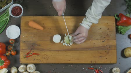 The chef cuts onions and carrots. Onions and carrots as an ingredient for making soup or another dish. Top view Stock mozgókép