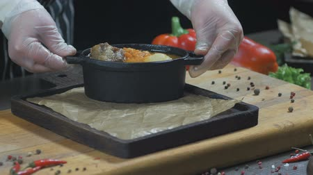 Chef is Serving soup with meat in iron saucepan. Wooden board Стоковые видеозаписи