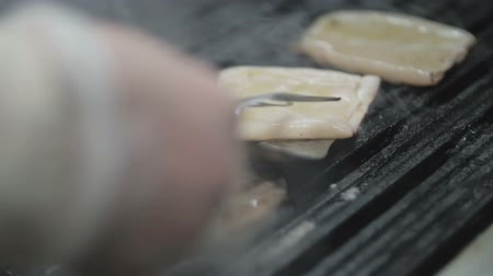 chobotnice : The chef is cooking squid on a barbeque grill