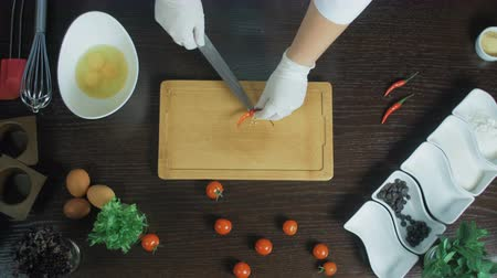Top view. Chef chopping a carrot with red pepper on cutting board. Remove seeds