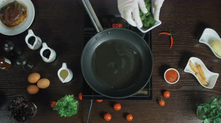 Sprouting broccoli frying in a pot with oil