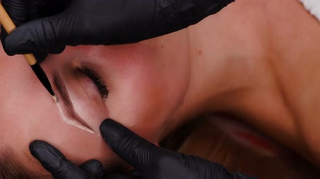 Professional specialist of permanent make-up in black gloves paint eyebrows.
