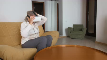 double happiness : Senior Woman Sitting On The Couch Playing VR Glasses. Good-looking Senior Woman In White Using VR 360 Glasses At Home.
