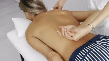 The orthopedist doctor does a backbone massage to a young woman. View from the side, the middle plan. Стоковые видеозаписи
