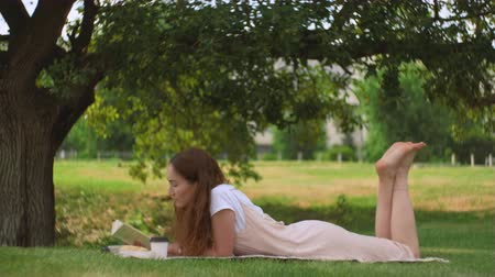 Young woman lying and reading a book under tree Стоковые видеозаписи