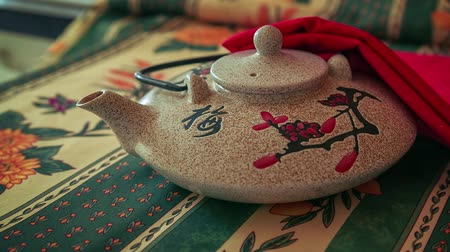 inspiração : Zoom out shot of Asian Teapot on a table with colorful green and yellow tablecloth