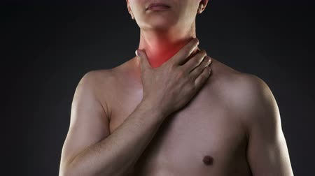 hrdlo : Sore throat, men with pain in the neck, black background, studio shot