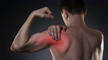 scoliosis : Man with pain in shoulder on black background, studio shot with red dot