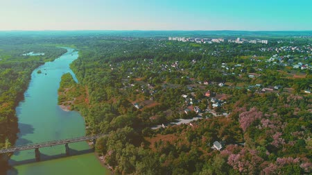 tag : Aerial establishing shot of a residential neighborhood, where a lot of house and mansions, wide river and the bridge over it are situated. 4K.