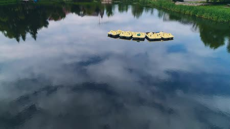 Aerial view of moving slowly paddleboats on the calm lake. 4K.