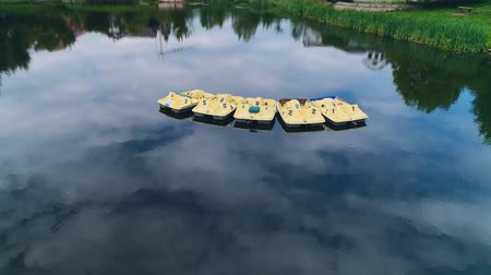 Drone view of lake, which reflects cloudy sky, and yellow paddleboats floating on it. 4K.