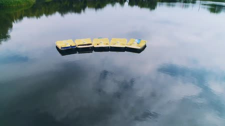 Flying over pedal boats on lake water, aerial panoramic video. 4K.