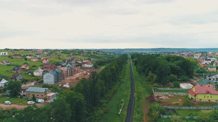 Aerial overhead view of townstreet rooftops residential houses parks commuter travel road and long rail.