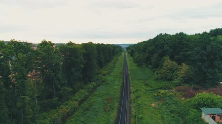 Aerial view, moving down, keeps in focus railtrack and shows marvellous countryside area, on green forest background.