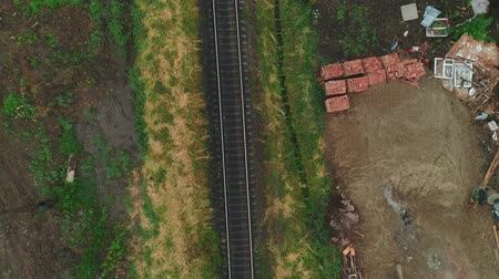 Aerial view of following old rusty abandoned rail tracks. 4K.