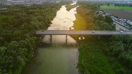 hmota : 4K aerial top down view of cars missing one another, driving along long bridge, over calm green water river. 4K.