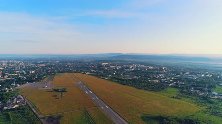 Aerial view of small aviation, located in close to town with amazing building and nature. 4K. Stock mozgókép