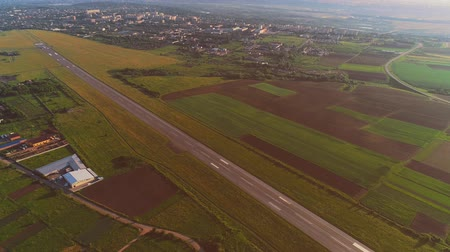 doména : Aerial view of small airport with take off runaway and white plane flying over. 4K.