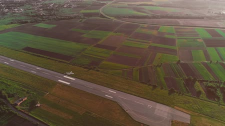 szybowiec : Aerial view of small airport with take off runaway and white plane flying over. 4K.