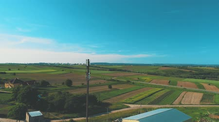 Aerial view of countryside life, fields are growing and cars are moving along the road. 4K.