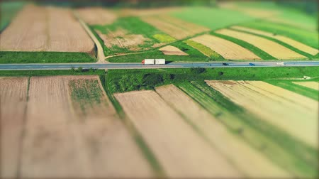 Aerial view of cars, moving on asphalt road through amazing landscape with fruitful fields. 4K.