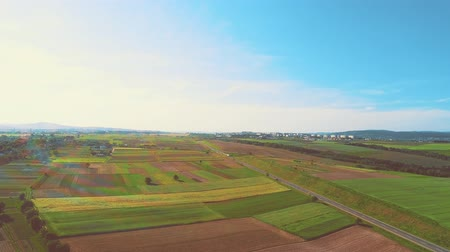 Aerial flight over the road between fields, there is rainbow blick on the beginning of the footage and blue sky is full of light and warmth. 4K. Stock mozgókép